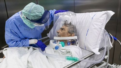 A nurse attends to a COVID-19 patient that is wearing a CPAP helmet while he is moved out of the Intensive Care Unit (ICU) of the Pope John XXIII Hospital on April 7, 2020 in Bergamo, Italy.
