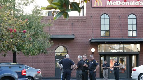 Police investigate at the scene following a lead of a man with a gun at a McDonald's in Ybor City in Tampa, (Gabriella Angotti-Jones/Tampa Bay Times via AP)