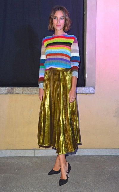 Alexa Chung uses her gamine sensibilities to combine a rainbow knit sweater with Michele's gold lamé skirt for surprisingly low-key results.