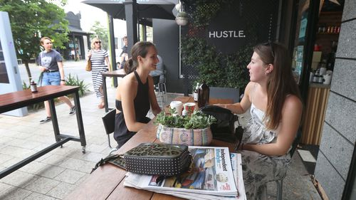 Two young women enjoy a catch up on King William Road in Hyde Park in Adelaide.