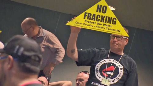 """Many in the audience held up """"anti-fracking"""" signs, protesting the NT Government's decision to allow the development of an onshore gas industry."""