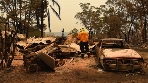 RFS Development Assessment & Planning Officer Adam Small inspects a burnt out home and out building near Balmoral during the Green Wattle Creek fire.