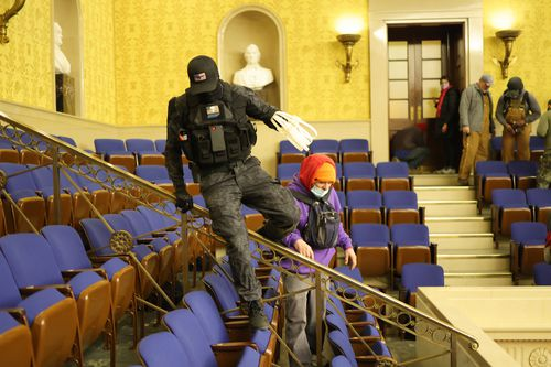 A protester carrying plastic zip-tie handcuffs is seen inside the Senate chamber, prompting theories some who stormed the building were ready and willing to capture hostages.
