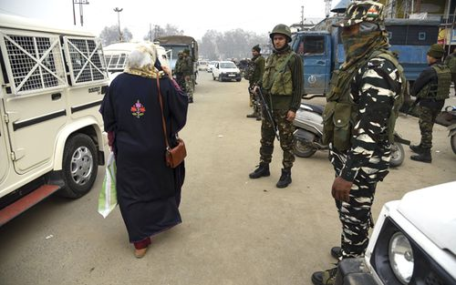 A Kashmiri woman walks past Indian Paramilitary forces standing guard close to the site of a blast in Indian controlled Kashmir. At least three people were wounded in a low-intensity blast in Srinagar city, on November 26.