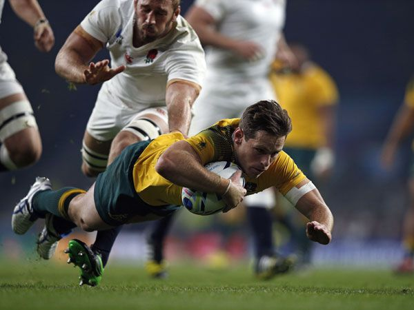 Wallbies flyhalf Bernard Foley dives over for his second try against England. (AFP