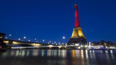 The Eiffel Tower is illuminated in the national colours of Belgium. (AAP)