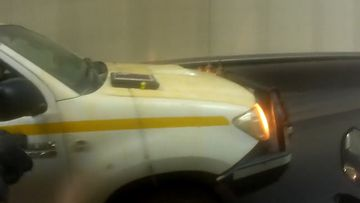 Motorbike rider passes laptop through car window while driving through Sydney tunnel.