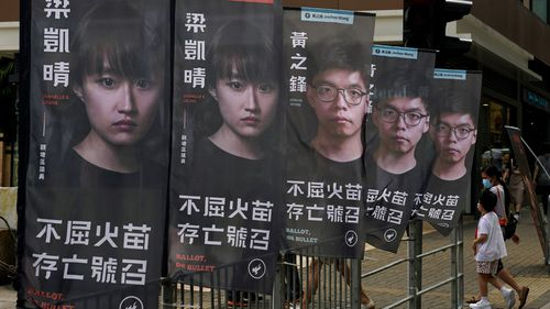 Banners of a pro-democracy candidate Joshua Wong, wearing glasses, are displayed outside a subway station in Hong Kong.