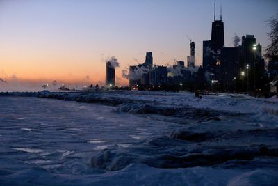 Ice forms along the shore of Lake Michigan before sunrise.