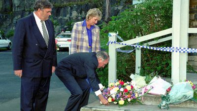 Australian Prime Minister John Howard lays flowers on the steps of the Broad Arrow Cafe in Port Arthur, as leader of the opposition Kim Beasley, left, and Senate leader Cheryl Kernot look on. The cafe was the site where 20 of the of the 35 massacre victims lost their lives.