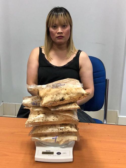 Ve Hi Tran pictured with the 1814 grams of heroin allegedly found in her luggage in Cambodia. (Image: Cambodia General Department of Immigration/Facebook)