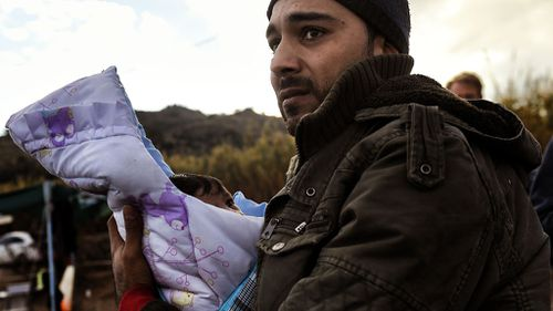 A migrant holding his baby, arrives along with other migrants and refugees, on the Greek island of Lesbos.  (AFP)