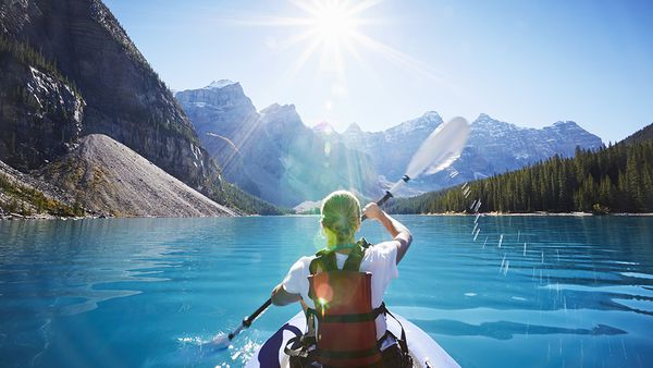 Kayaking the glacial waters of Moraine Lake, Banff National Park, Canada.