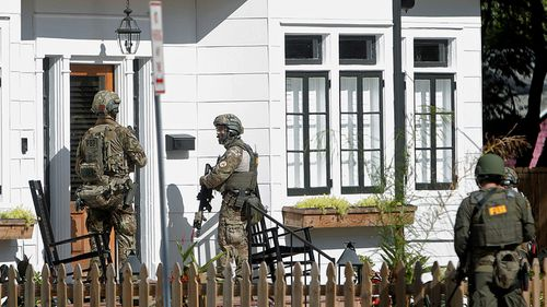 Armed police carry out door-to-door inquiries after the latest Florida shooting on Tuesday. (Photo: AP).