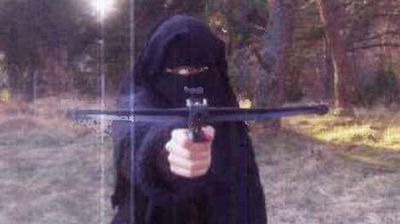 Hayat Bomeddiene aims a small crossbow directly at the camera in a chilling photo that emerged earlier today as police announced they were searching for her. (Le Monde)