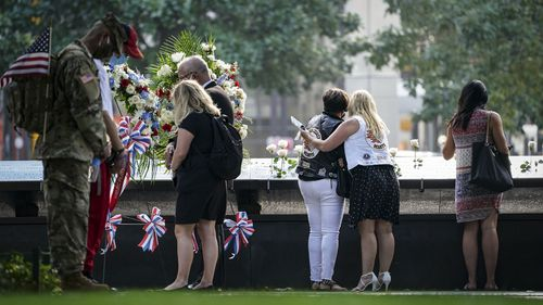 Mourners pause during a moment of silence at the National September 11 Memorial and Museum, Friday, Sept. 11, 2020, in New York