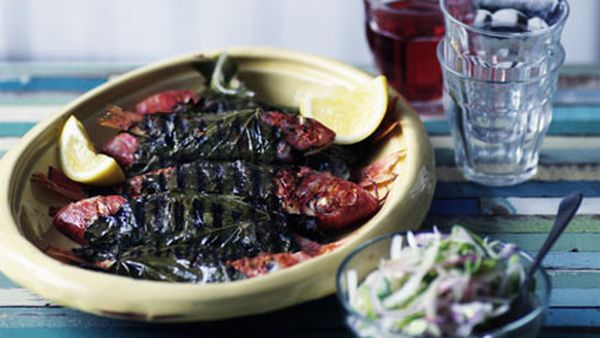 Barbecued barbounia in vine leaves with onion salad