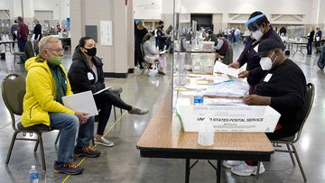 Election workers verify ballots as recount observers, left, watch during a Milwaukee hand recount of presidential votes.
