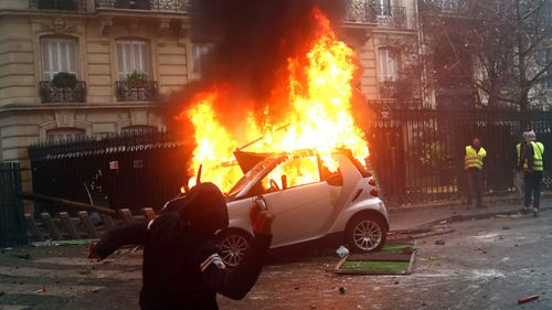 Protesters walked past a car on fire