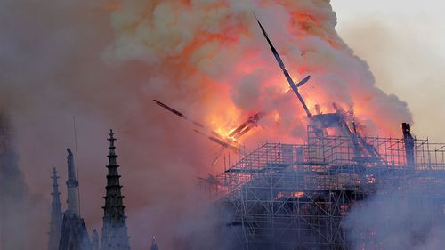 The spire leaned to one side and tumbled onto the burning frame of the building below.