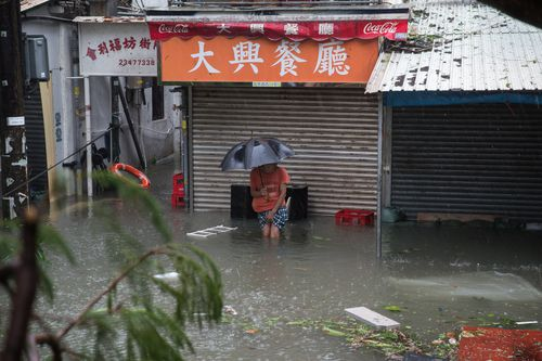 A local resident ventures out in the floods in Lei Yu Mun, HK.