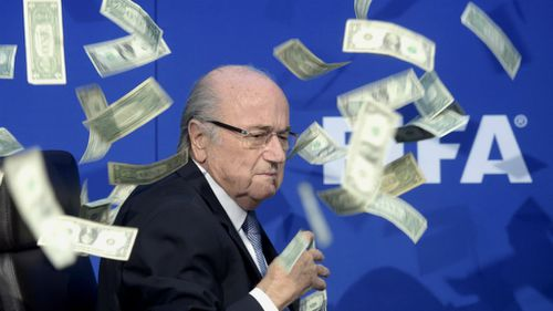FIFA president Sepp Blatter reacts while banknotes are thrown at him during a press conference. (AAP)