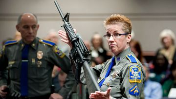 Firearms training unit Detective Barbara J. Mattson, of the Connecticut State Police, holds up a Bushmaster AR-15 rifle, produced by Remington Arms and the same make and model of gun used by Adam Lanza in the Sandy Hook School shooting