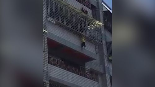 A Taiwanese toddler was seen dangling from a fifth-floor balcony by his head over the weekend in a freak accident. Picture: Taiwan Fun 666 via Storyful.