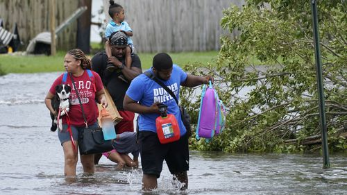 Michael Thomas, back, carries his daughter Mikala, out of his flooded neighborhood after Hurricane Ida moved through on Monday (local time).