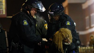 Police arrest a female protester in Ferguson. (Getty Images)