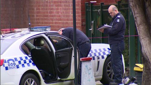 Forensic police examine the car driven by the police officer who was shot. (9NEWS)