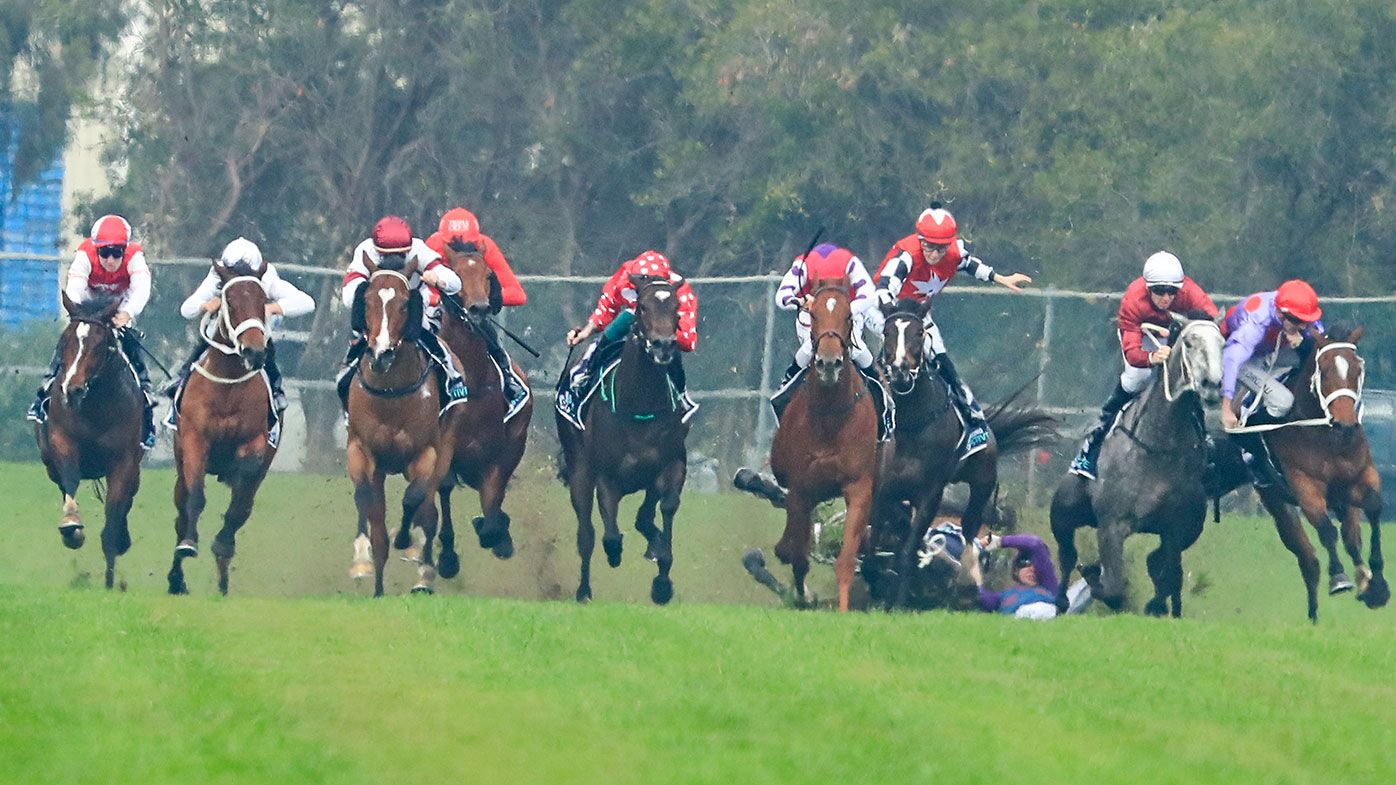 Jockey Andrew Adkins crashes to the turf during the opening race at Rosehill.