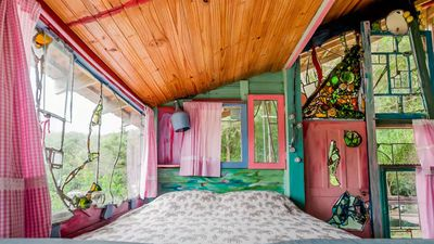"""<p>This<a href=""""https://www.airbnb.com.au/rooms/172391"""" draggable=""""false"""">colourful cabin in Brazil</a>has stained glass windows and walls studded with glass bottles.</p> <p>$51 AUDper night<br /> <br /> Photo: Airbnb</p>"""