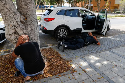 People take cover as a siren sounds a warning of incoming rockets fired from the Gaza strip, in the southern Israeli town of Ashkelon.