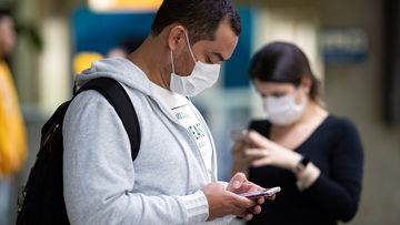 Passengers wearing masks as a precaution against the spread of the new coronavirus COVID-19 use their phones at the Sao Paulo International Airport in Sao Paulo, Brazil, Thursday, Feb. 27, 2020. (AP Photo/Andre Penner)