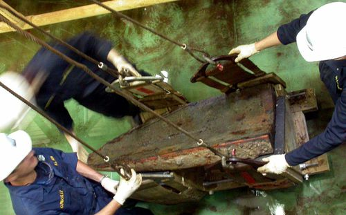 Workers lifting a keel block from the Hunley submarine. (Photo: AP).