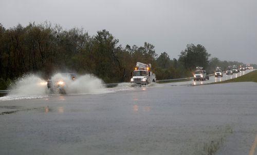 Power company trucks make their way through water on highway US 17 near Jacksonville, North Carolina.