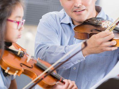 Man teaching girl violin