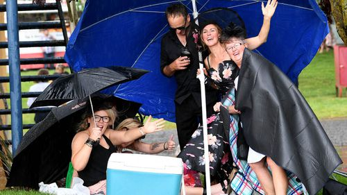 Racegoers get caught out in a spurt of heavy rain during the Ballarat Cup Day at the Ballarat Turf Club in Ballarat, Saturday, November 25, 2017.