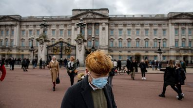 A man wears a face mask as he walks past Buckingham Palace as the outbreak of coronavirus intensifies
