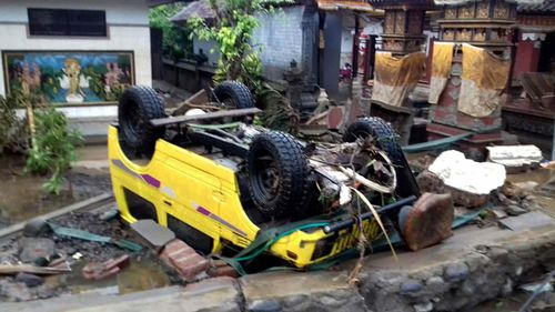 A car was thrown onto its roof by the force of the wave sweeping through coastal villages.