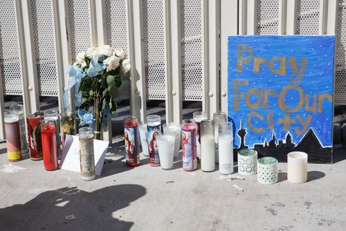 Candles, flowers and signs line the sidewalk near the Stratosphere Tower as part of a makeshift memorial to the victims of the mass shooting. (AAP)