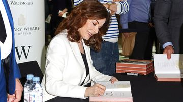 Lawson signs a copy of her new book 'At My Table'. (AAP)