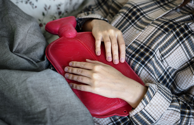 Woman using hot water bottle