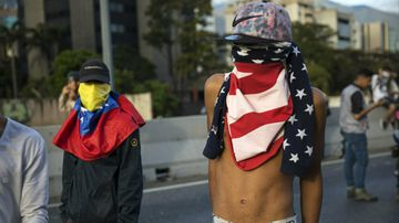 An anti-government protester using a US flag as a mask stands with a small group of demonstrators who were returning from a peaceful demonstration called by self-declared interim president Juan Guaido to demand the resignation of President Nicolas Maduro, in Caracas, Venezuela.