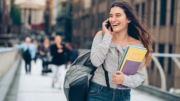 Smiling student walking and talking on the phone