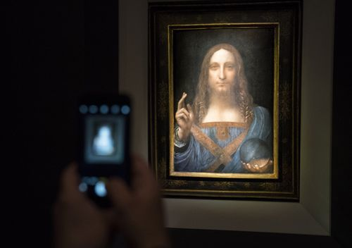 A visitor takes a photo of the painting 'Salvator Mundi' by Leonardo da Vinci at Christie's New York Auction House. (Getty)