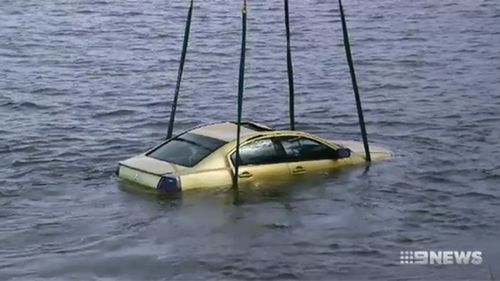The Mitsubishi sedan reversed suddenly into a river.