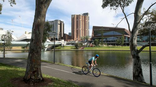 A man cyclists rides along the Torrens River on November 20, 2020 in Adelaide, Australia