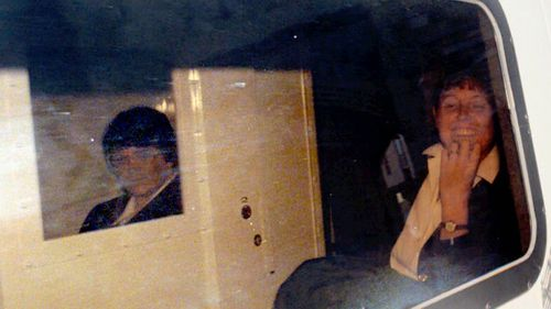 Rosemary West (left) sitting in a box within the police van that drove her from Winchster Crown Court, southern England, in 1995.